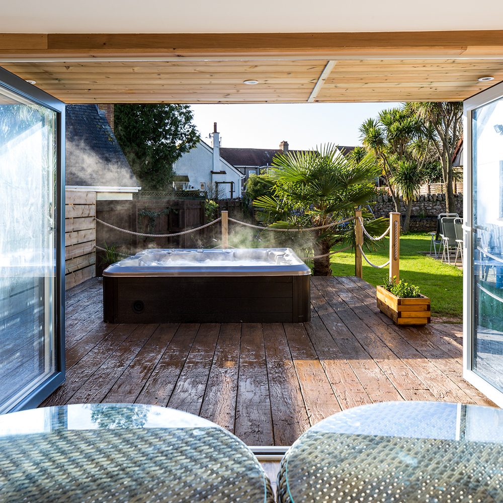 A Hydropool self-cleaning hot tub, as seen from one of our garden rooms. Both are available from our Bristol showroom.