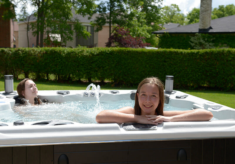 Young adults in hot tub in sunny garden