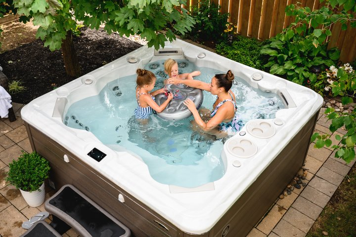 Hydropool lifestyle image, hot tub in garden with family in summer playing cards