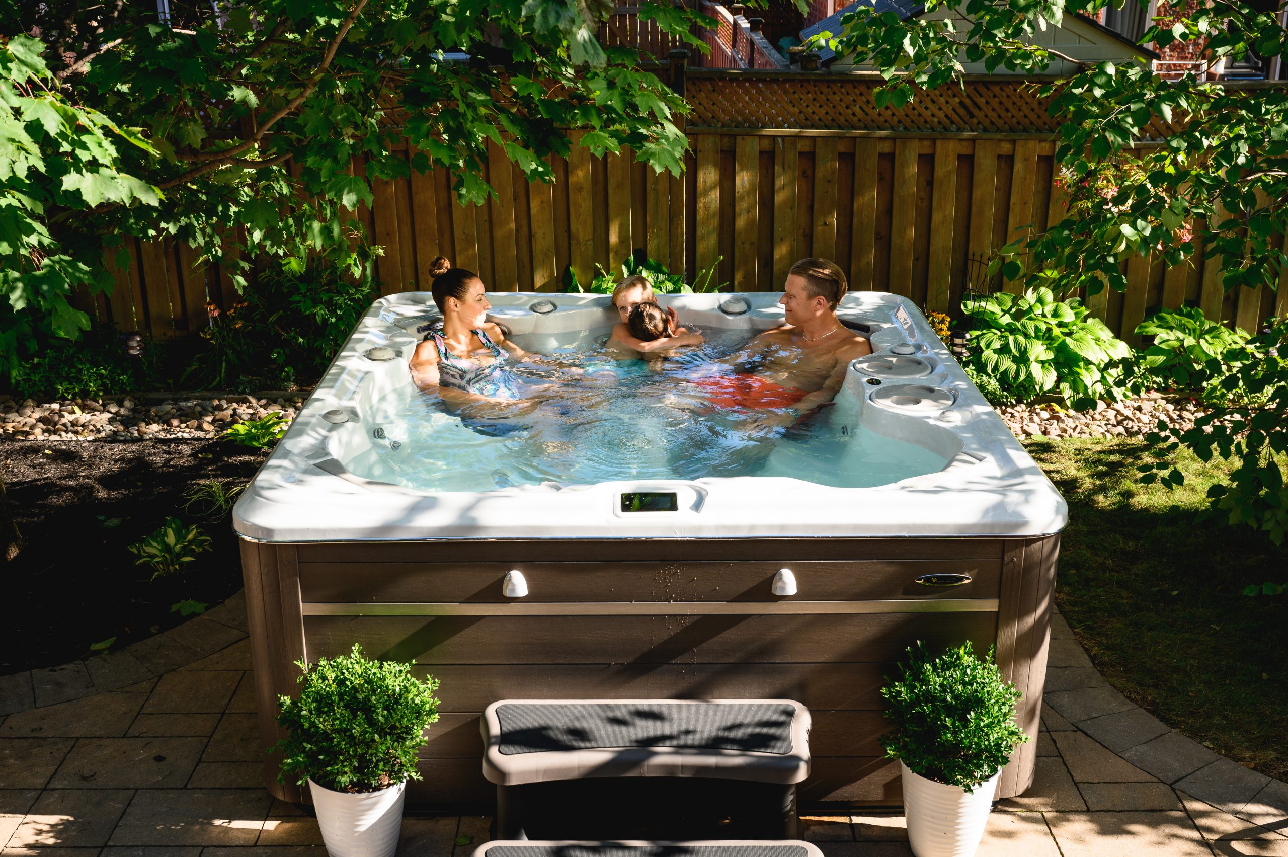 Hydropool lifestyle image, hot tub in garden with family in summer