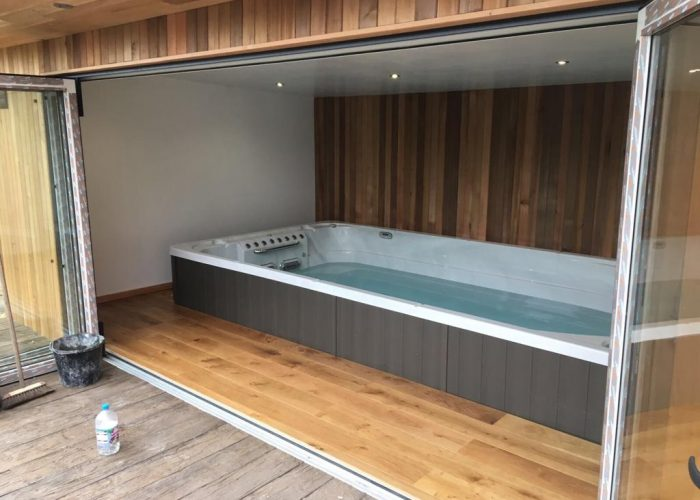 Swim spa in garden room with decking